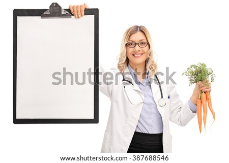 Female doctor holding a clipboard and a bunch of fresh carrots isolated on white background - stock photo