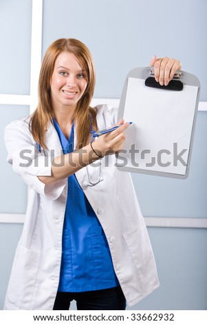 Female doctor holding blank chart in modern hospital - stock photo