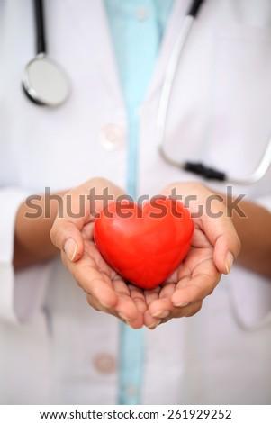 Female doctor holding red heart shape - stock photo