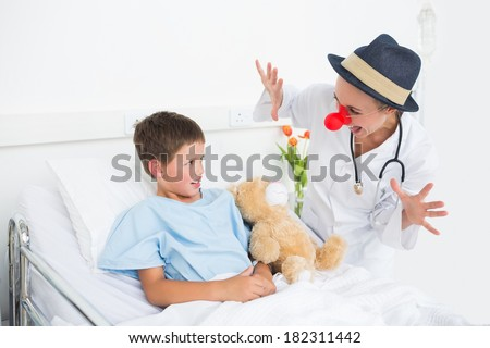 Female doctor in clown costume entertaining ill boy in hospital bed - stock photo