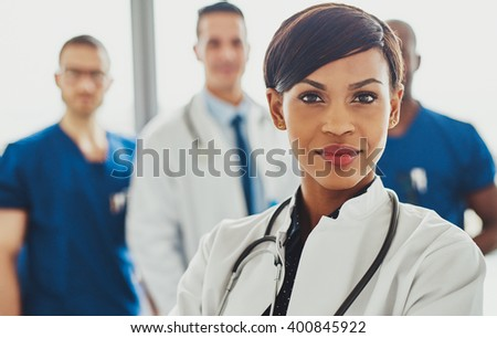 Female doctor in front of team, stethoscope around neck looking confident - stock photo