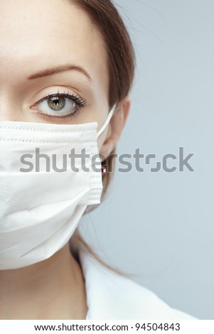 Female doctor in protective mask on a blue background - stock photo