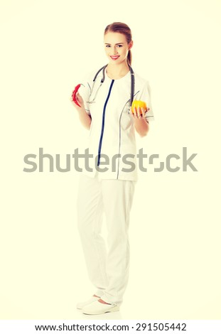 Female doctor in uniform holding pepper and chilli - stock photo