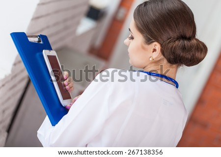 Female doctor looking at medical records on tablet computer at hospital - stock photo