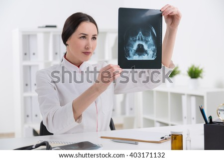 Female doctor looking at xray in office - stock photo