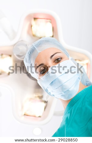 female doctor looking down at patient in operation room - stock photo