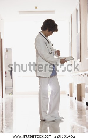 Female doctor looking through her notes - stock photo