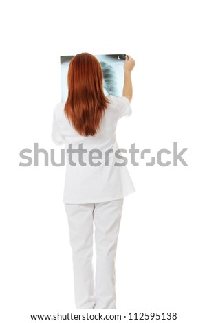 Female doctor or nurse looking at radiography photo , isolated