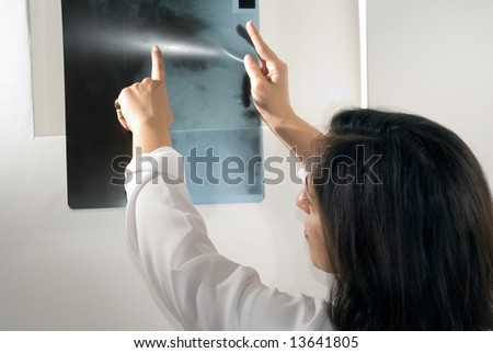 Female Doctor points to an x-ray. Horizontally framed photograph