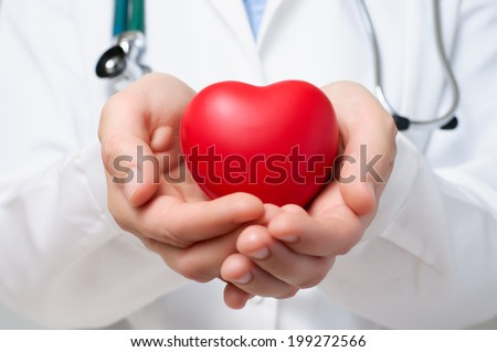Female doctor protecting a red heart with her hands - stock photo