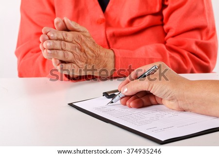 Female doctor's hand filling the medical record - stock photo