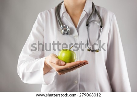 Female doctor's hand holding green apple. Close up shot on grey blurred background. Concept of Healthcare And Medicine. Copy space - stock photo