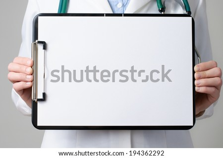 Female doctor showing a clipboard with blank paper - stock photo