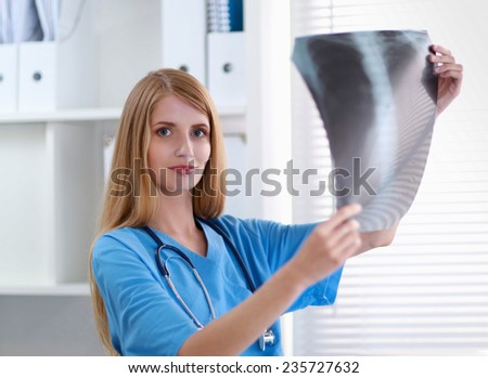 Female doctor showing x-ray at hospital - stock photo