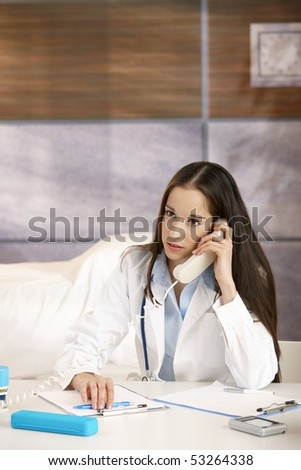 Female doctor sitting at desk in doctor's room talking on phone. Copyspace above head.