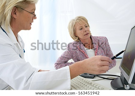 female doctor sitting at her desk pointing to a computer screen explaining something to a senior woman patient  - stock photo