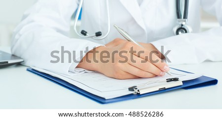 Female doctor sitting at the table and filling up medical application form. Health care, insurance and help concept.