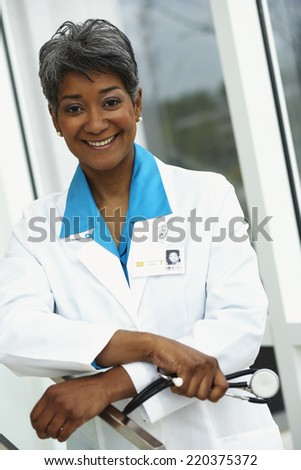 Female doctor smiling at camera - stock photo