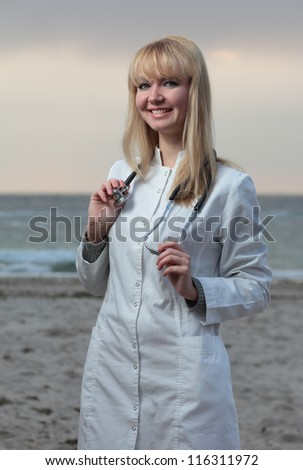 Female doctor smiling on the background of the sea.