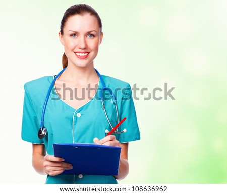 Female doctor smiling to you, green blurred background - stock photo
