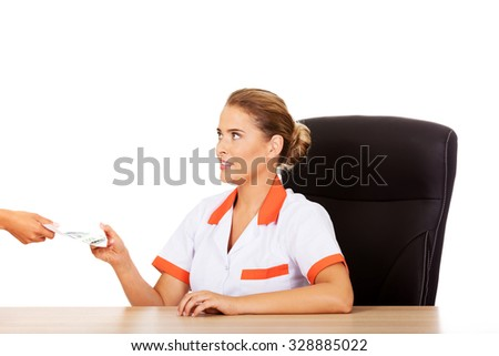 Female doctor take money from patient. - stock photo