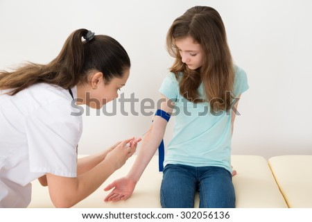 Female Doctor Taking Blood Sample With Syringe From Patient In Hospital - stock photo