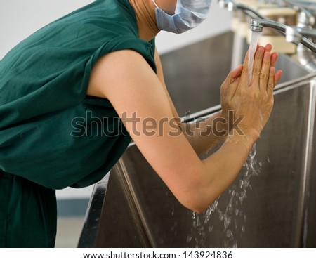 Female doctor washing hands before operation. - stock photo