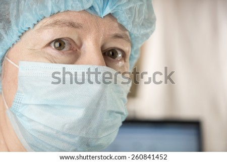 Female doctor wearing medical mask and surgical cap looking seriously and worried at patient with computer in background - stock photo