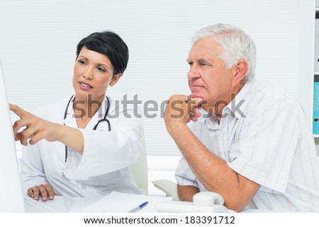 Female doctor with male patient reading reports on computer at medical office - stock photo