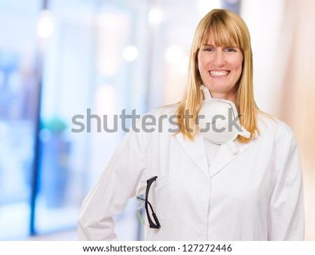 Female Doctor With Protective Mask Around Neck in a room - stock photo