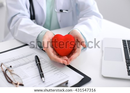 Female doctor with stethoscope holding heart.    - stock photo