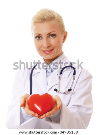 Female doctor with stethoscope holding heart and sitting at desk isolated on white background.