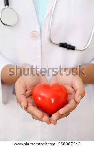 Female doctor with stethoscope holding red heart shape - stock photo