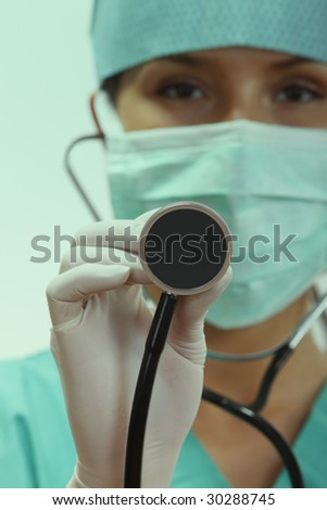 Female doctor with stethoscope in an emergency room lighting environment.Selective focus on the stethoscope. - stock photo