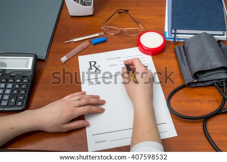 female doctor writing prescription paper with medical tools - stock photo