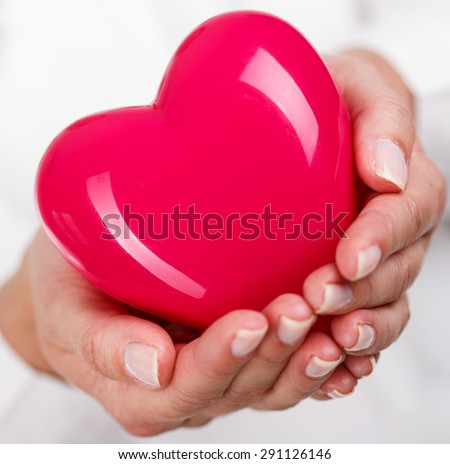Female doctors's hands holding and covering red toy heart. Doctor's hands closeup. Medical help, prophylaxis or insurance concept. Cardiology care,health, protection and prevention - stock photo