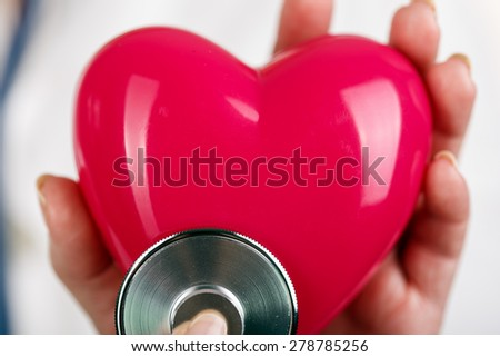 Female doctors's hands holding red toy heart and putting stethoscope's head close to it. Medical help or insurance concept. Cardiology care and health. Heart surgery and resuscitation concept - stock photo