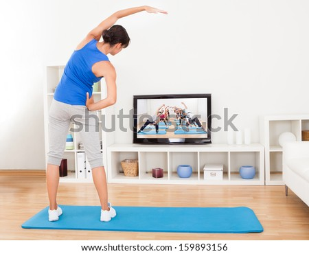 Female Doing Fitness Exercise In Front Of Television - stock photo