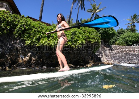 female doing stand up paddle surfing