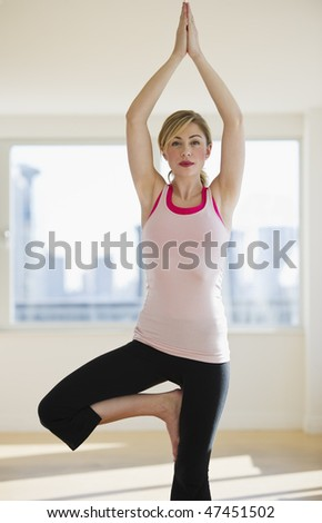female doing yoga on mat alone in studio