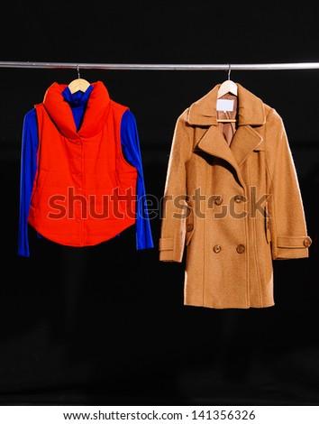 female dress and coat isolated on hanging-black background - stock photo