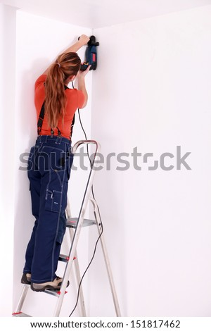 Female drilling roof - stock photo