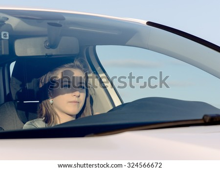 Female driver checking her side mirror as she pulls away into the street after being parked alongside a rural road