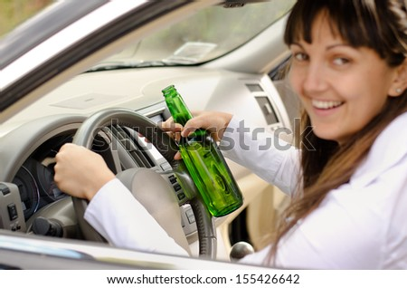 Female driver drinking and driving while grinning out of the side window as she clutches the steering wheel with her bottle of alcohol clasped in one hand - stock photo