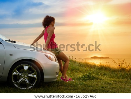 Female driver enjoying freedom and beautiful sunshine over the sea after driving to coast in summer vacation travel. Woman relaxing and taking a break to enjoy the scenery. - stock photo