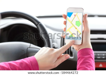 female driver hand holding a phone with interface navigator on a screen  - stock photo