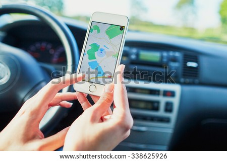 Female driver hands holding a phone with interface navigator on a screen - stock photo