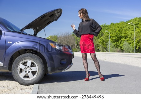 Female driver inspects her car engine. Lady dressed in provocative clubbing pantyhose and bright red shoes high heels mini skirt stays near car opening engine hood - stock photo
