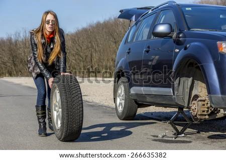 Female driver repairs car. Young female, dressed biker style, rolls big wheel towards broken car - stock photo