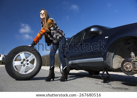 Female driver repairs car. Young female, dressed in jeans pants, red sweater and fur vest, rolls big wheel away from the broken car. Bright blue sky, sun shining day